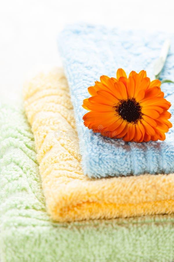 Ζωηρόχρωμες πετσέτες και πορτοκαλί λουλούδι στοκ φωτογραφία