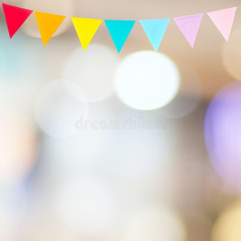 Ζωηρόχρωμες σημαίες κομμάτων που κρεμούν στο αφηρημένο υπόβαθρο θαμπάδων, birthd στοκ φωτογραφία