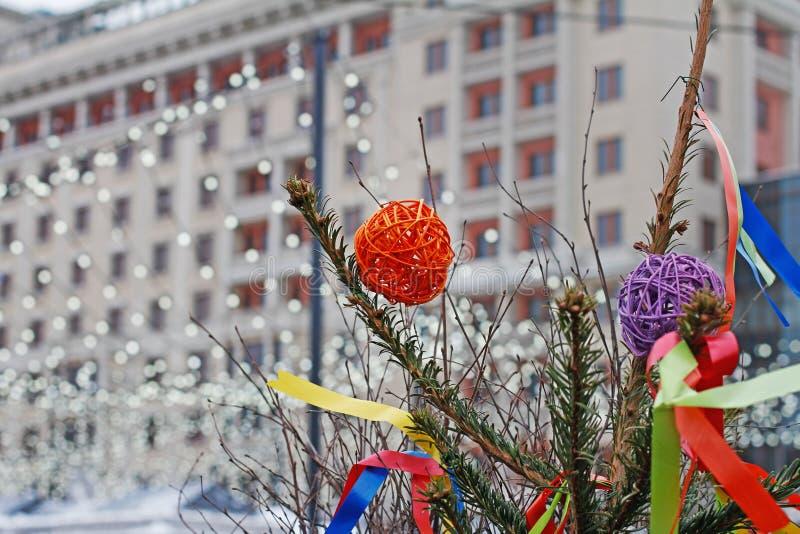 Ζωηρόχρωμες σφαίρες ινδικού καλάμου που κρεμούν σε ένα χριστουγεννιάτικο δέντρο με τις κορδέλλες στο υπόβαθρο της γιρλάντας Χριστ στοκ φωτογραφίες