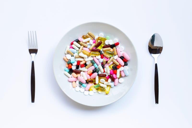 Ζωηρόχρωμες ταμπλέτες με τις κάψες και τα χάπια στο άσπρο πιάτο, λαός και κουτάλι στο λευκό στοκ εικόνα με δικαίωμα ελεύθερης χρήσης
