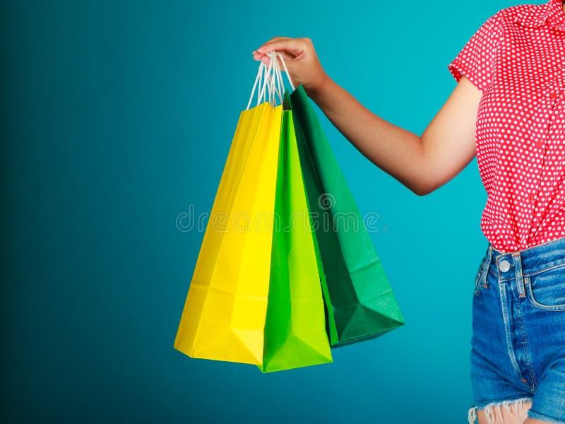 Ζωηρόχρωμες τσάντες αγορών στο θηλυκό χέρι Λιανική πώληση πώλησης στοκ φωτογραφίες