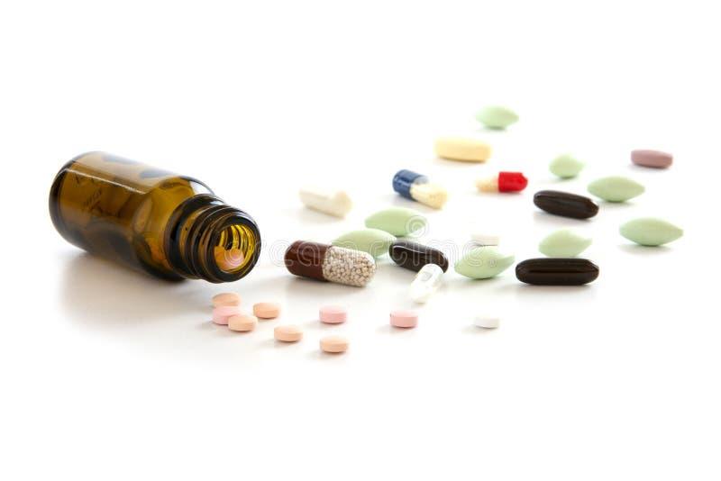 Ζωηρόχρωμες χάπια και κάψες και ένα να βρεθεί μπουκάλι φαρμακείων που απομονώνεται στοκ εικόνα με δικαίωμα ελεύθερης χρήσης