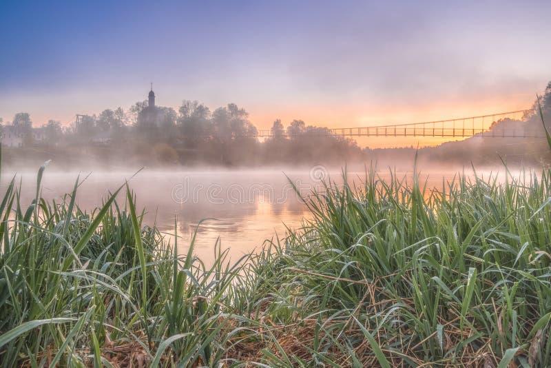 Ζωηρόχρωμη άποψη της γέφυρας εκκλησιών και αναστολής από τις αντίθετες όχθεις του ποταμού στοκ φωτογραφία
