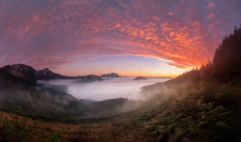 Ζωηρόχρωμη ανατολή πέρα από την κοιλάδα Aramaiona κάτω από την ομίχλη στοκ φωτογραφία