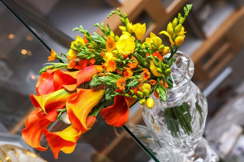 Ζωηρόχρωμη ανθοδέσμη των πορτοκαλιών calla κρίνων και άλλων λουλουδιών στον πίνακα στοκ φωτογραφία με δικαίωμα ελεύθερης χρήσης
