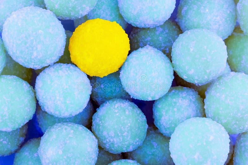 Ζωηρόχρωμη αντιπαραβαλλόμενη κίτρινη στρογγυλή καραμέλα υποβάθρου μπλε dragees υποβάθρου γλασαρισμένο φωτεινό σε έναν εορταστικό  στοκ φωτογραφίες
