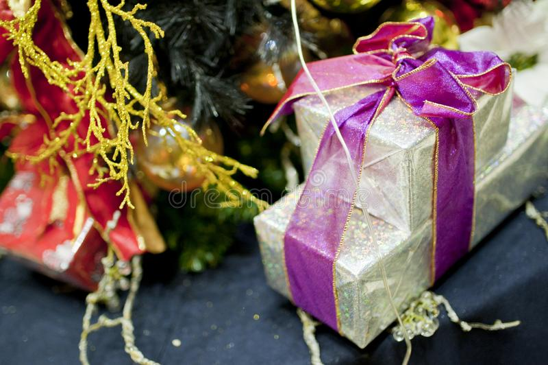 Ζωηρόχρωμη διακόσμηση Χριστουγέννων κάτω από το χριστουγεννιάτικο δέντρο με το βολβό φω'των στοκ φωτογραφία