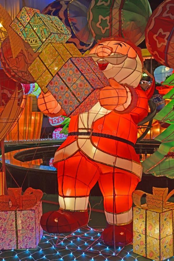 Ζωηρόχρωμη ελαφριά διακόσμηση του γέλιου Άγιου Βασίλη που φαίνεται ευτυχείς φέρνοντας σωροί των κιβωτίων δώρων στοκ φωτογραφία
