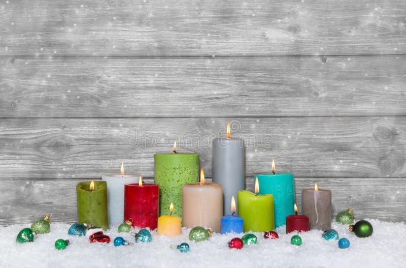 Ζωηρόχρωμη διακόσμηση Χριστουγέννων με τα διαφορετικά κεριά στο γκρι και στοκ εικόνα με δικαίωμα ελεύθερης χρήσης