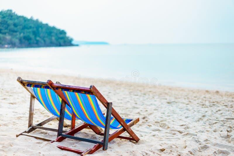 Ζωηρόχρωμη καρέκλα παραλιών στην παραλία με τον όμορφο μπλε ουρανό την ηλιόλουστη ημέρα, που χαλαρώνει στις καρέκλες παραλιών στοκ φωτογραφία