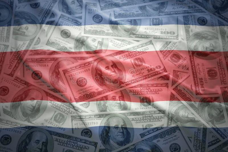 Ζωηρόχρωμη κυματίζοντας από την Κόστα Ρίκα σημαία σε ένα υπόβαθρο χρημάτων δολαρίων στοκ φωτογραφία