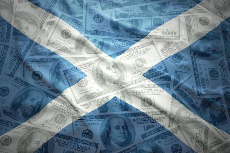 Ζωηρόχρωμη κυματίζοντας σκωτσέζικη σημαία σε ένα υπόβαθρο χρημάτων δολαρίων στοκ εικόνες