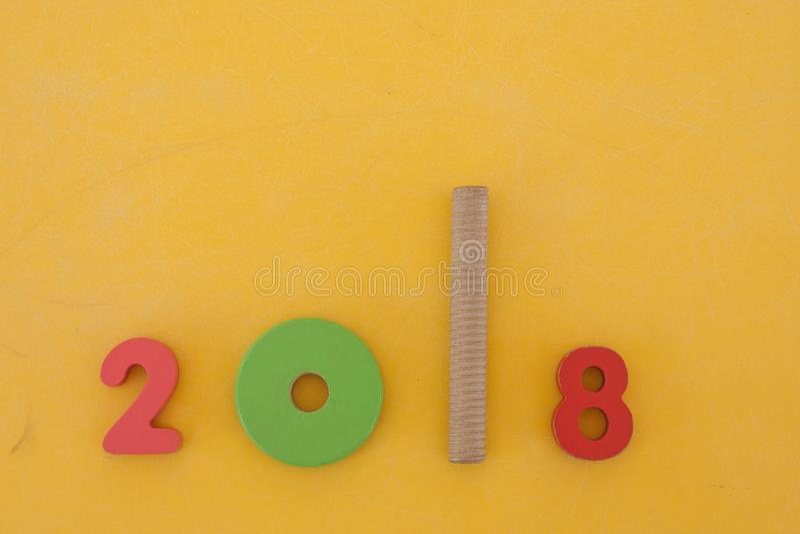 Ζωηρόχρωμη νέα διατύπωση έτους 2018 που γίνεται από τα παιχνίδια παιδιών που θέτουν στο κίτρινο υπόβαθρο στο εκλεκτής ποιότητας ύ στοκ εικόνα
