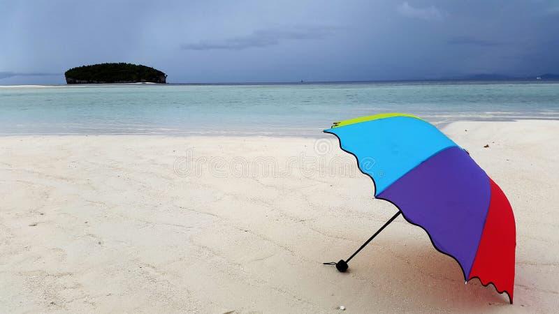 Ζωηρόχρωμη ομπρέλα που καθορίζει στην ακτή που περιβάλλεται από την άσπρη άμμο και την μπλε παραλία στοκ εικόνα με δικαίωμα ελεύθερης χρήσης