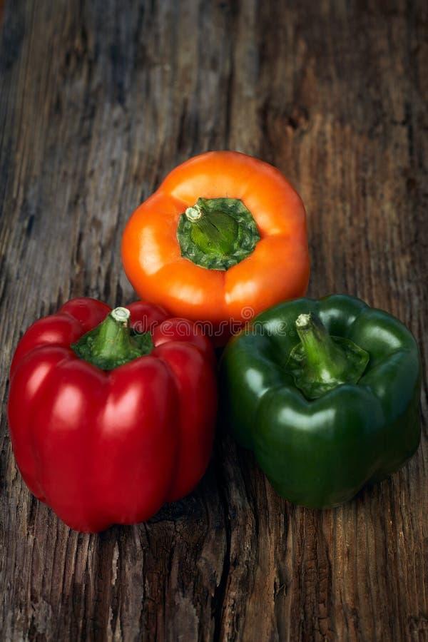Ζωηρόχρωμη πάπρικα πράσινων, κίτρινων, και κόκκινων πιπεριών στο υπόβ στοκ εικόνα