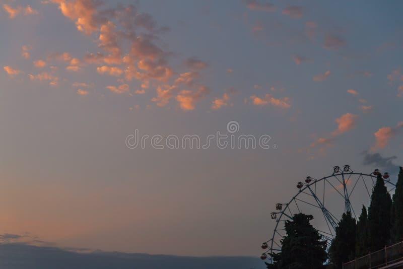 Ζωηρόχρωμη περιστροφή ροδών Ferris αργά στο λούνα παρκ με τον ουρανό στο υπόβαθρο Ο γύρος στο ιπποδρόμιο αντιπροσωπεύει στοκ φωτογραφία με δικαίωμα ελεύθερης χρήσης