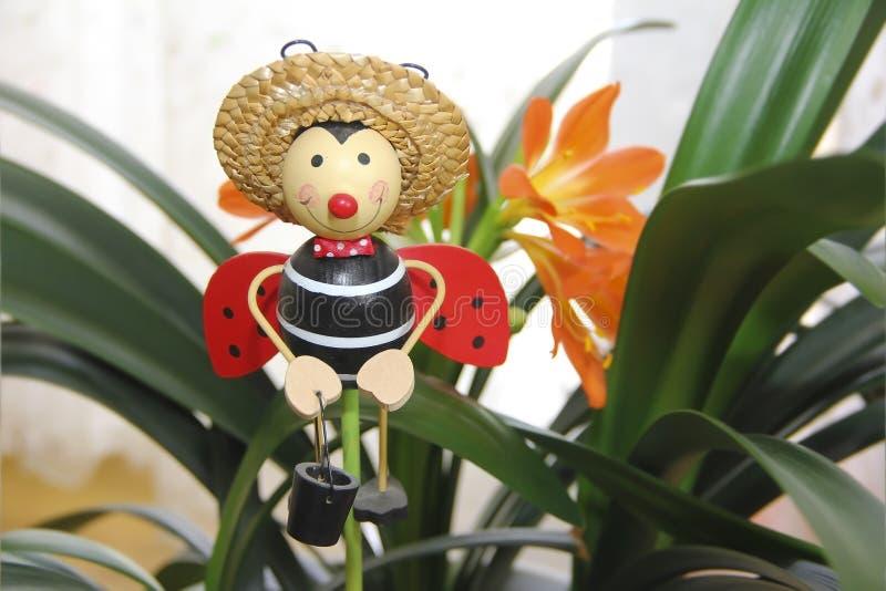 Ζωηρόχρωμη πεταλούδα παιχνιδιών κήπων σε ένα καπέλο σε ένα υπόβαθρο των πορτοκαλιών κρίνων και των πράσινων φύλλων στοκ φωτογραφίες