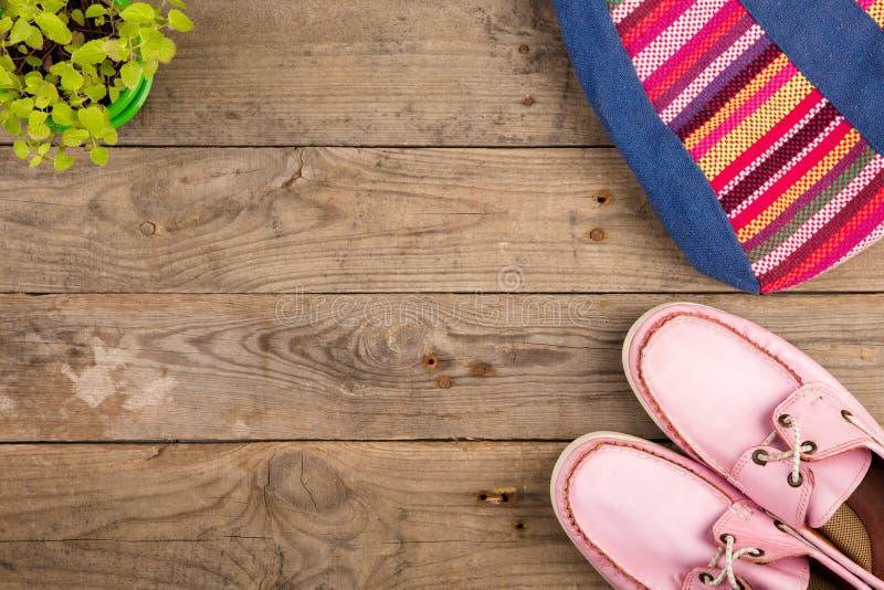ζωηρόχρωμη τσάντα, ρόδινα παπούτσια και λουλούδια στο ξύλινο γραφείο στοκ εικόνα με δικαίωμα ελεύθερης χρήσης