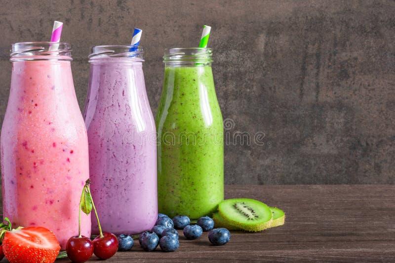 Ζωηρόχρωμοι καταφερτζήδες στα μπουκάλια, την υγιεινή διατροφή βιταμινών detox ή τα vegan ποτά με τα φρούτα, τα μούρα και τα άχυρα στοκ εικόνες