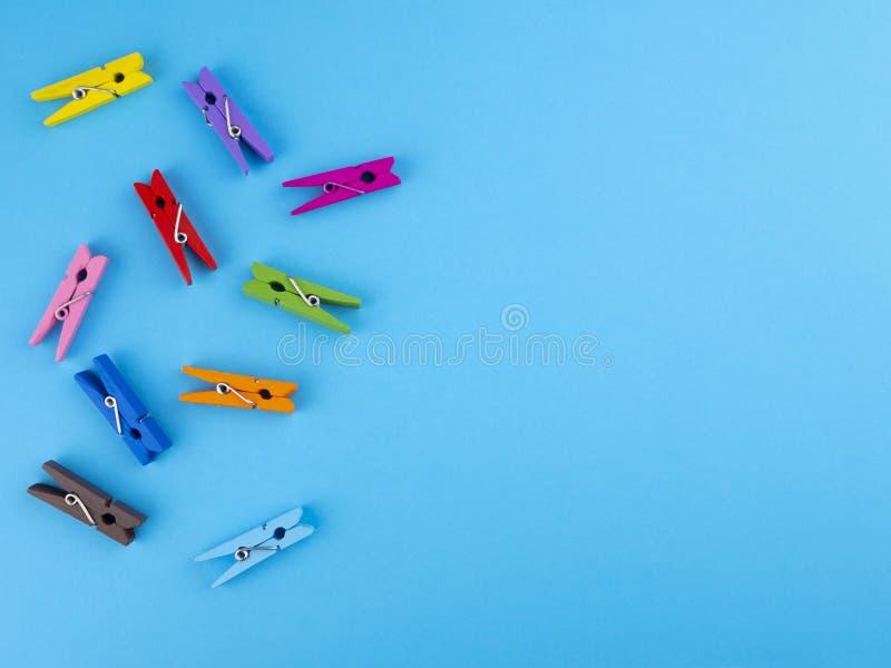 Ζωηρόχρωμοι ξύλινοι γόμφοι clothespins σε ένα μπλε υπόβαθρο στοκ φωτογραφίες με δικαίωμα ελεύθερης χρήσης