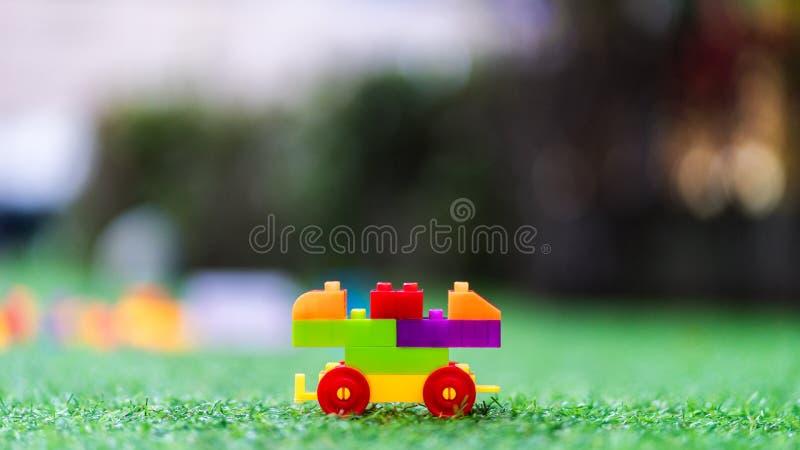 Ζωηρόχρωμοι πλαστικοί φραγμοί παιχνιδιών που συγκεντρώνονται για να στηριχτούν ένα αυτοκίνητο στο playgrou στοκ εικόνες