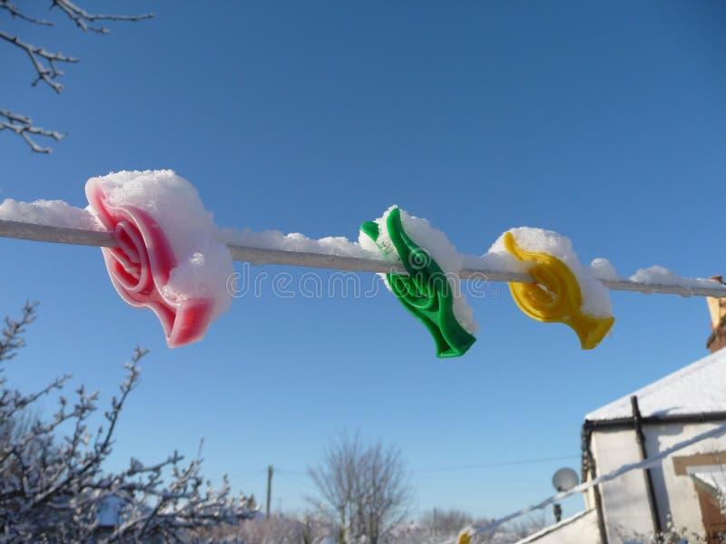 Ζωηρόχρωμοι πλαστικοί γόμφοι ενδυμάτων που συσσωματώνονται στο χιόνι στοκ φωτογραφίες με δικαίωμα ελεύθερης χρήσης