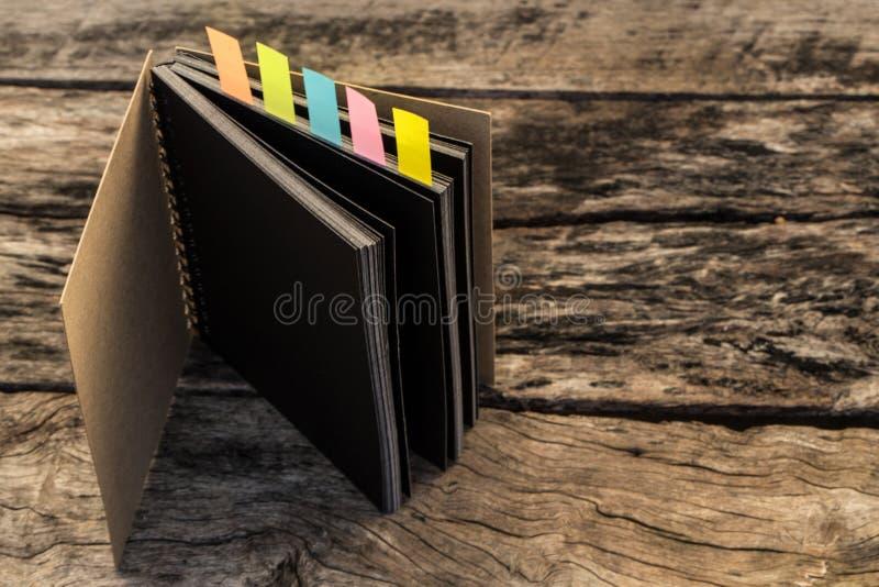 Ζωηρόχρωμοι σελιδοδείκτες για τα έγγραφα με το σημειωματάριο, κινηματογράφηση σε πρώτο πλάνο του colo στοκ εικόνα