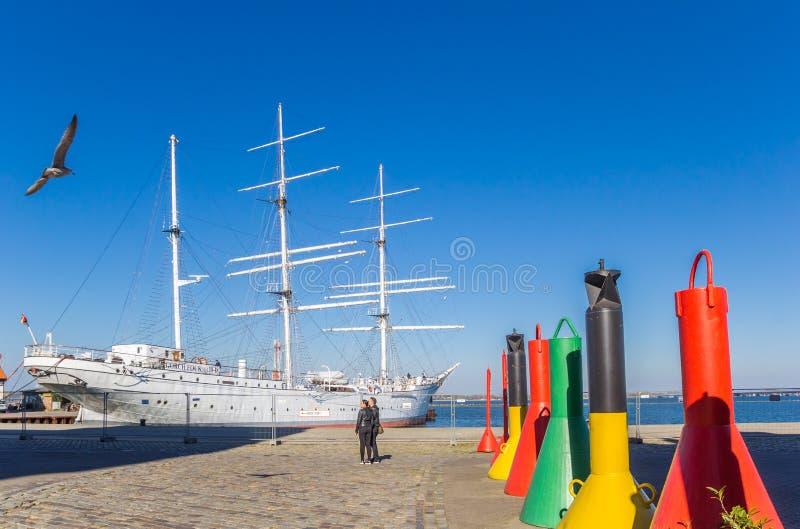 Ζωηρόχρωμοι σημαντήρες μπροστά από το σκάφος Gorch Fock σε Stralsund στοκ εικόνες