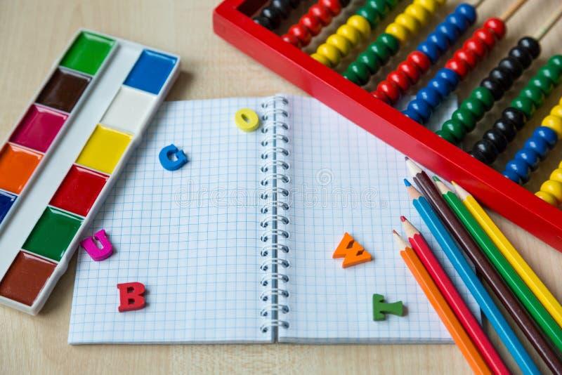 Ζωηρόχρωμος άβακας, μολύβια, ρολόι, πίνακας κιμωλίας στο ξύλινο υπόβαθρο Εκπαίδευση, πίσω στο σχολείο στοκ εικόνες