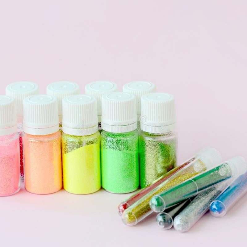 Ζωηρόχρωμος ακτινοβολεί ψέματα στο ρόδινο υπόβαθρο κρητιδογραφιών Πολλά στρογγυλά βάζα με τα πολύχρωμα φωτεινά σπινθηρίσματα για  στοκ εικόνα με δικαίωμα ελεύθερης χρήσης