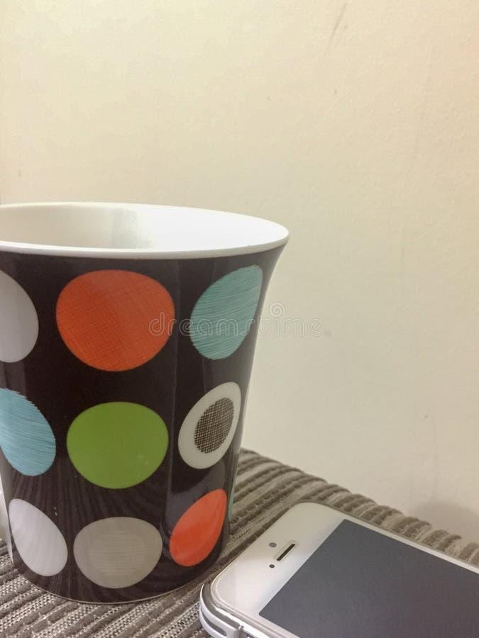 Ζωηρόχρωμος διαστιγμένος καφές και κινητό τηλέφωνο στοκ εικόνες