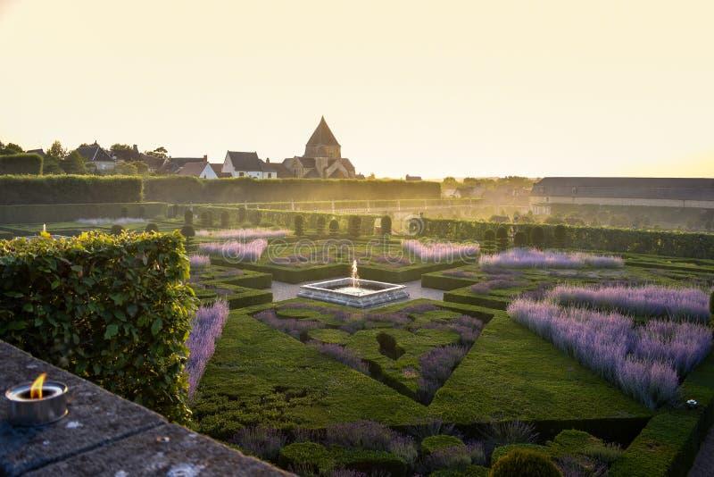 Ζωηρόχρωμος επίσημος κήπος στο ηλιοβασίλεμα, με ένα μυστήριο φως στοκ εικόνες