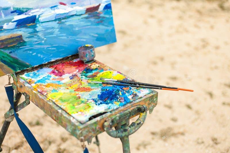 Ζωηρόχρωμος εργασιακός χώρος του καλλιτέχνη με τις βούρτσες και τα ελαιοχρώματα υπαίθρια στοκ εικόνες
