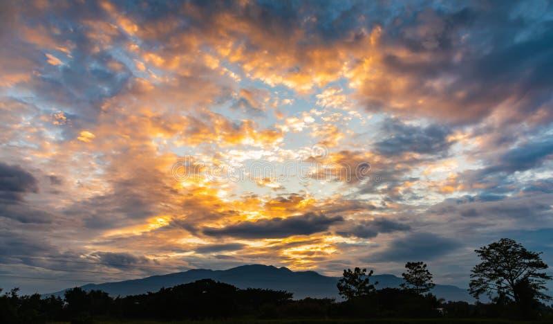 Ζωηρόχρωμος νεφελώδης ουρανός ηλιοβασιλέματος με τη σκιαγραφία του βουνού και του δάσους στοκ φωτογραφία με δικαίωμα ελεύθερης χρήσης
