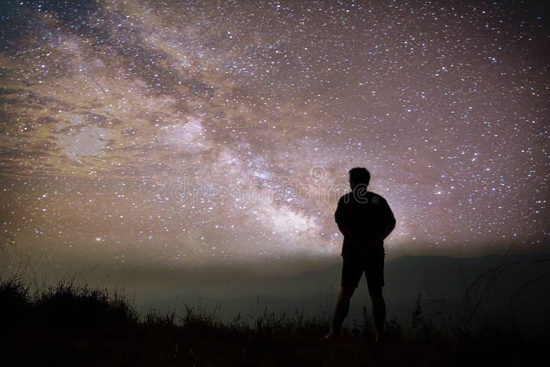 Ζωηρόχρωμος νυχτερινός ουρανός με τα αστέρια και τη σκιαγραφία ενός μόνιμου ατόμου στην πέτρα Μπλε γαλακτώδης τρόπος με το άτομο  στοκ εικόνα