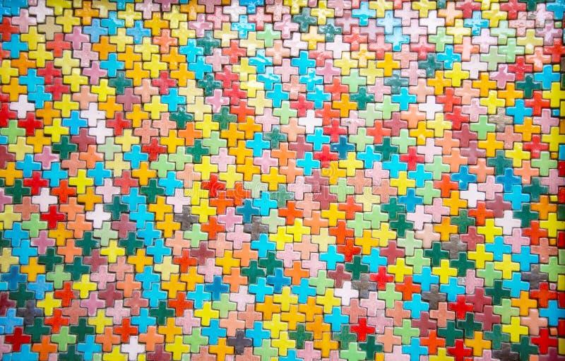 Ζωηρόχρωμος συν το τούβλο μορφής στον τοίχο: Κινηματογράφηση σε πρώτο πλάνο στοκ φωτογραφία