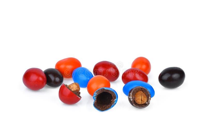 Ζωηρόχρωμος των καραμελών σοκολάτας που γεμίζονται με τα καρύδια που απομονώνονται στοκ εικόνα