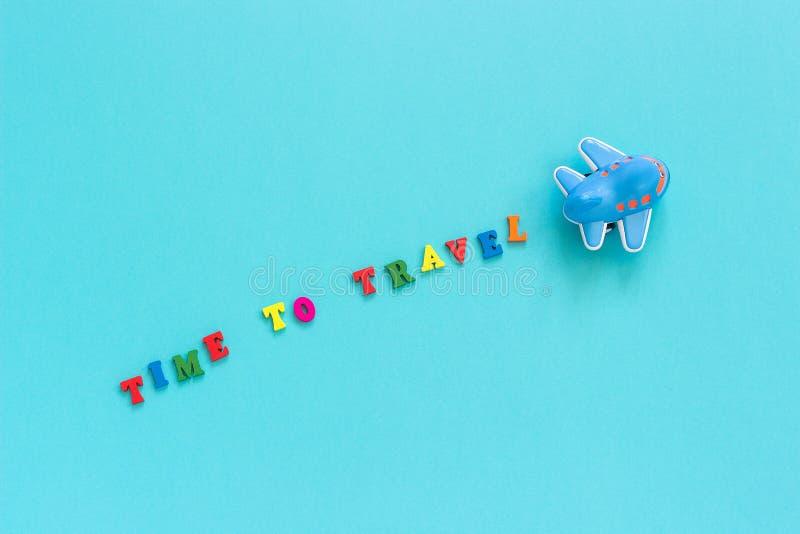 Ζωηρόχρωμος χρόνος κειμένων να ταξιδεψει και αστείο αεροπλάνο παιχνιδιών των παιδιών στο μπλε υπόβαθρο εγγράφου Διαστημική τοπ έν στοκ εικόνα με δικαίωμα ελεύθερης χρήσης