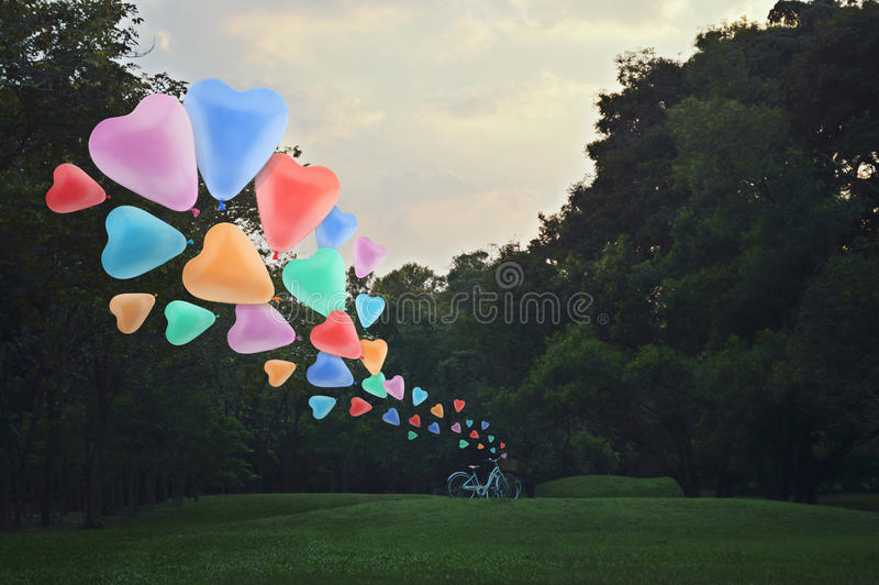 Ζωηρόχρωμο επιπλέον σώμα μπαλονιών αγάπης καρδιών στον αέρα με το ποδήλατο στο πάρκο στοκ φωτογραφία με δικαίωμα ελεύθερης χρήσης