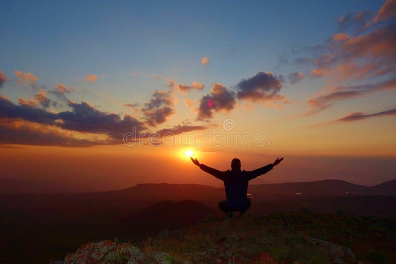 Ζωηρόχρωμο ηλιοβασίλεμα με έναν νεαρό άνδρα στην άκρη του ηφαιστείου Azhdahak στα βουνά Geghama, Αρμενία στοκ φωτογραφίες