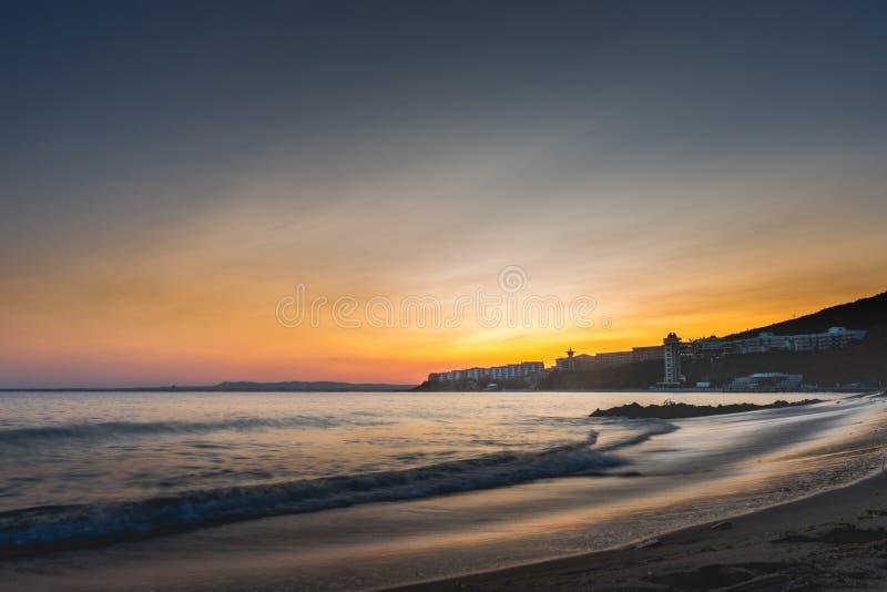 Ζωηρόχρωμο ηλιοβασίλεμα πέρα από την παραλία κόλπων θάλασσας στη Βουλγαρία με την πόλη Nessebar στο cinematic βλέμμα στοκ φωτογραφία με δικαίωμα ελεύθερης χρήσης
