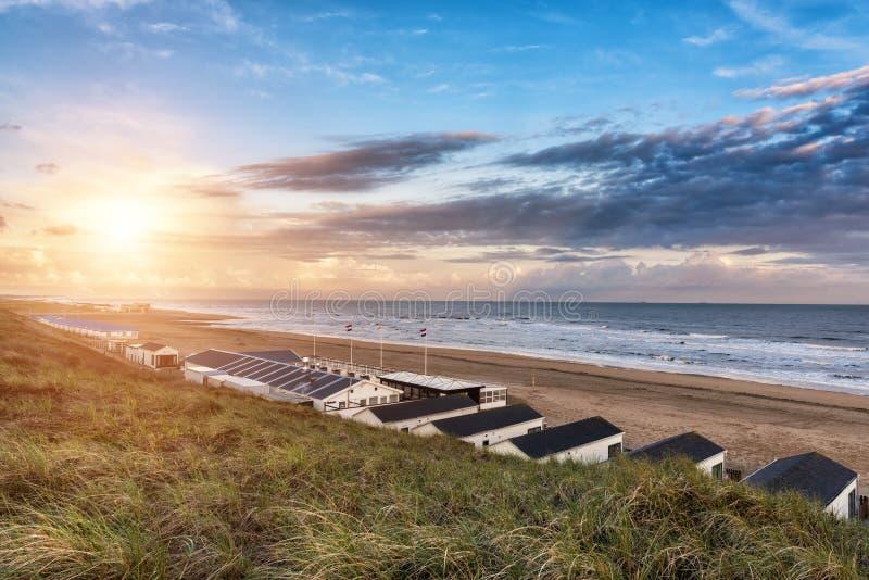 Ζωηρόχρωμο ηλιοβασίλεμα πέρα από τη θάλασσα και την αμμώδη παραλία στις Κάτω Χώρες στοκ φωτογραφία
