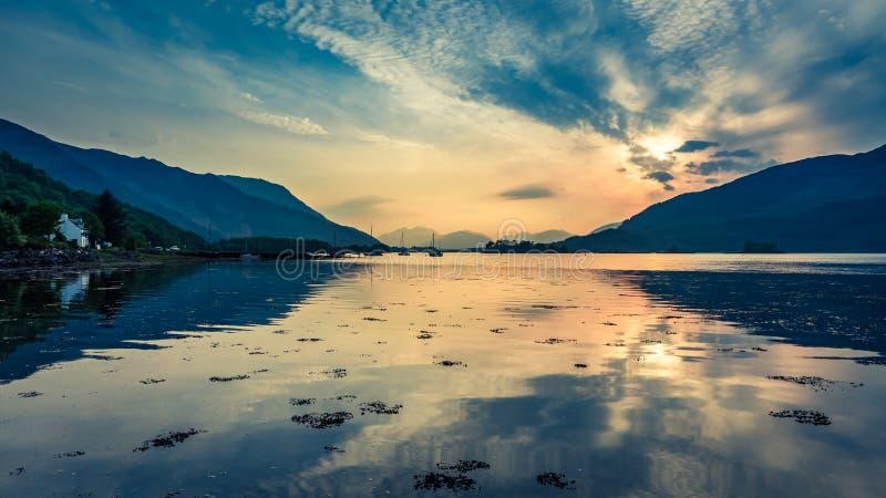 Ζωηρόχρωμο ηλιοβασίλεμα πέρα από τις βάρκες στη λίμνη στη Σκωτία στοκ εικόνες