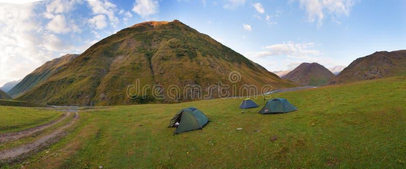 Ζωηρόχρωμο θερινό πανόραμα με τις πράσινες σκηνές τουριστών στην κοιλάδα κάτω από τα βουνά κάτω από το μπλε ουρανό Όμορφες άγρια  στοκ φωτογραφία με δικαίωμα ελεύθερης χρήσης