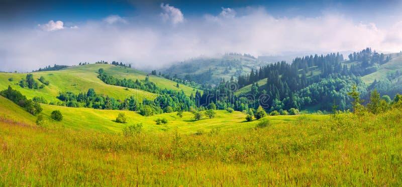 Ζωηρόχρωμο θερινό πανόραμα του ομιχλώδους ορεινού χωριού στοκ φωτογραφία με δικαίωμα ελεύθερης χρήσης