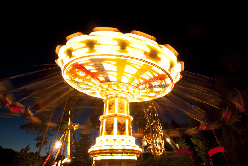 Ζωηρόχρωμο ιπποδρόμιο ταλάντευσης αλυσίδων στην κίνηση στο λούνα παρκ τη νύχτα στοκ φωτογραφία