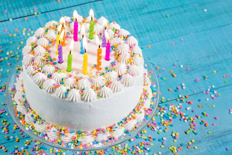 Ζωηρόχρωμο κέικ γενεθλίων με τα κεριά στοκ εικόνες