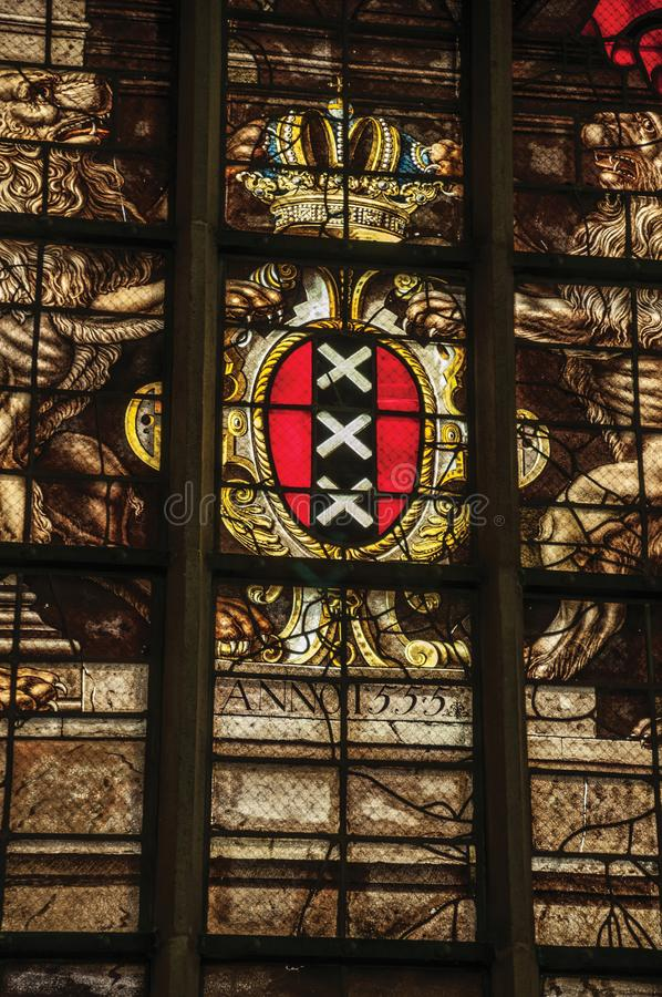 Ζωηρόχρωμο λεκιασμένο παράθυρο γυαλιού μέσα στη γοτθική παλαιά εκκλησία με την κάλυψη των όπλων του Άμστερνταμ στοκ εικόνα