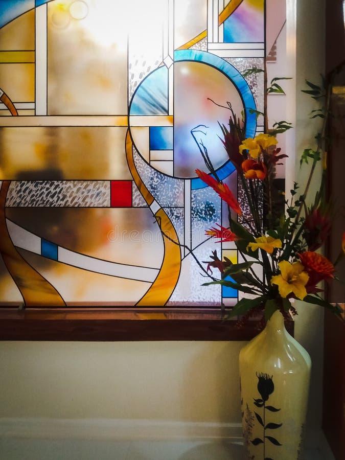 Ζωηρόχρωμο λεκιασμένο παράθυρο γυαλιού με τη ρύθμιση λουλουδιών στο άσπρο διακοσμητικό βάζο στοκ φωτογραφία με δικαίωμα ελεύθερης χρήσης