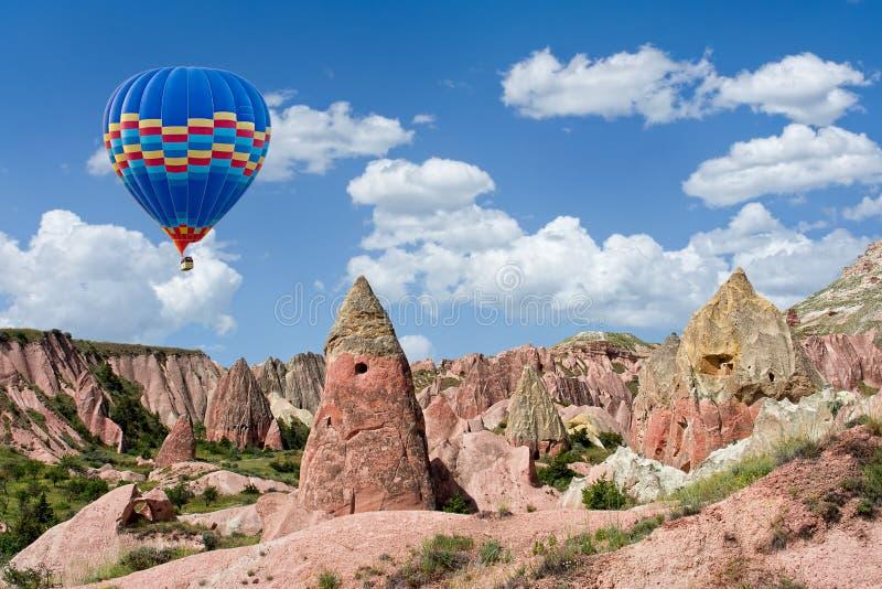 Ζωηρόχρωμο μπαλόνι ζεστού αέρα που πετά πέρα από την κόκκινη κοιλάδα σε Cappadocia, Α στοκ φωτογραφία